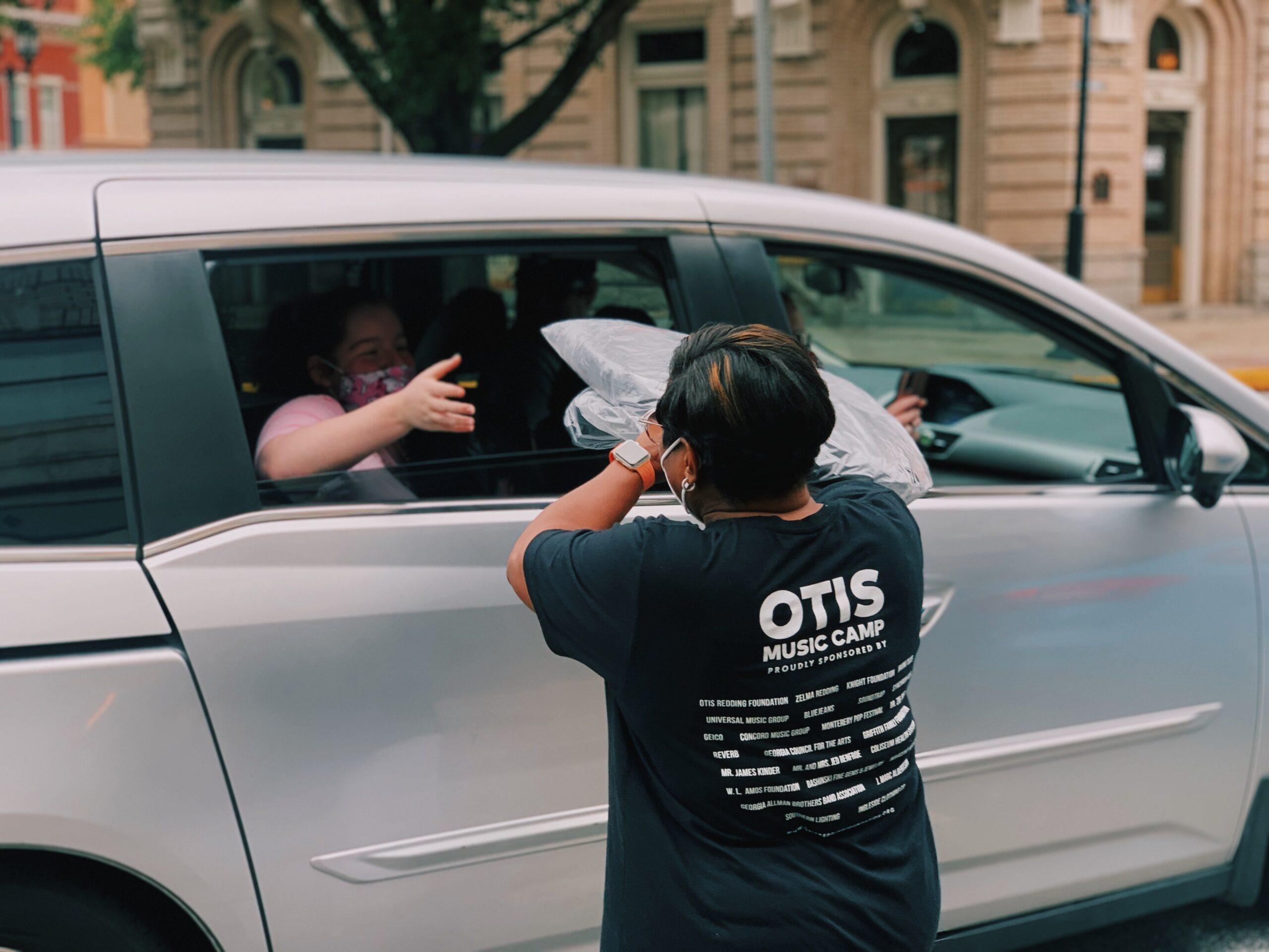 Otis Redding Foundation VP/executive director Karla Redding-Andrews hands an OMC 2.0 gift bag to camper Jena Branch.