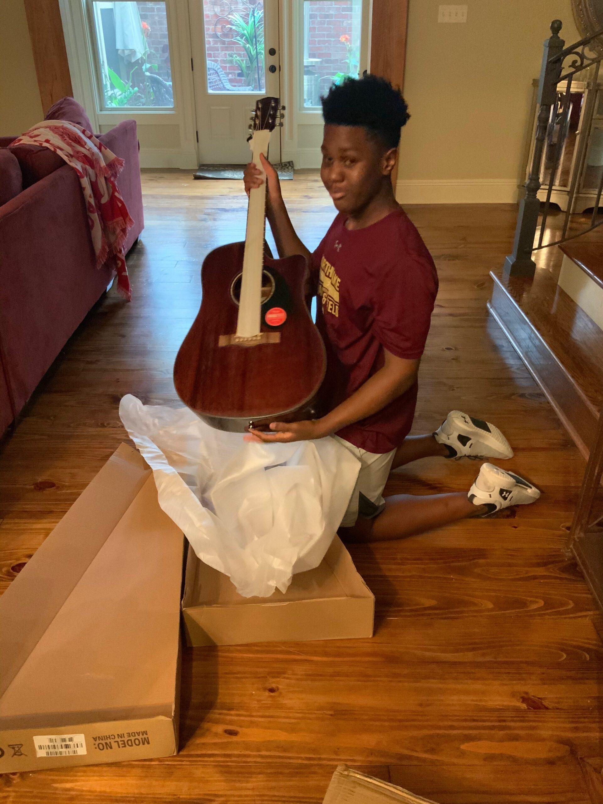 Elijah Jackson unwraps his new Fender acoustic guitar.